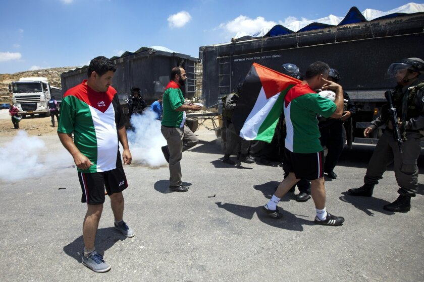 Israeli border policeman and Palestinian protesters argue during a demonstration in support for dozens of Palestinian hunger strikers in Israeli jails, outside Ofer military prison, near the West Bank city of Ramallah, Wednesday, June 11, 2014. A day before the start of the World Cup in Brazil, protesters dressed up in the jerseys of the Palestinian football team and kicked a ball around outside Ofer, an Israeli lockup in the West Bank. A group of helmeted soldiers prevented them from advancing. Troops fired stun grenades and pushed some of the players who dribbled and kicked the ball over the heads of soldiers. (AP Photo/Majdi Mohammed)