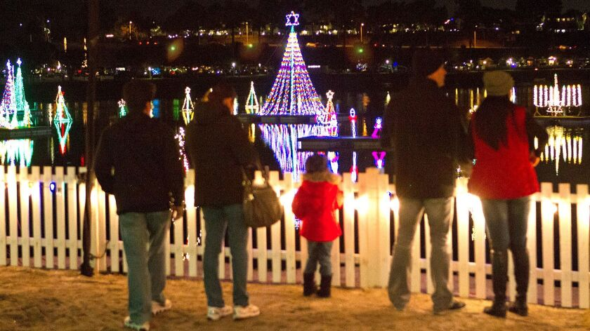 Families gathers to observe the row of christmas tree shaped light decorations at the Newport Dunes
