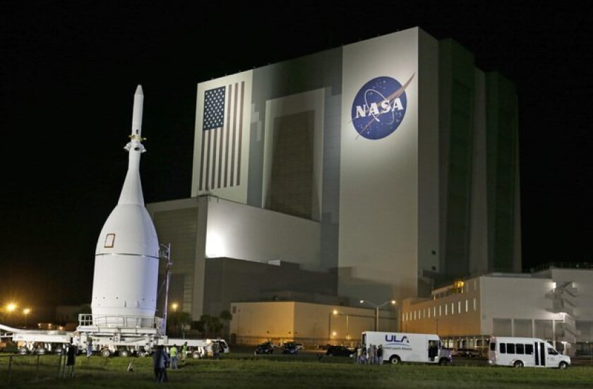 The Orion Spacecraft moves by the Vehicle Assembly Building on its approximately 22 mile journey from the Launch Abort System Facility at the Kennedy Space Center to Space Launch Complex 37B at the Cape Canaveral Air Force Station, in Cape Canaveral, Fla. The test flight for Orion is scheduled to l
