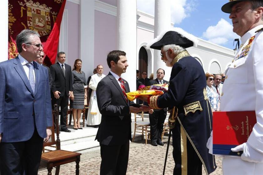 El cónsul de España Eduardo Garrigues (c-d), le entrega al senador José Nadal Power (c-i), la bandera que cubrió los restos restos del puertorriqueño Ramón Power y Giralt, junto al gobernador Alejandro García Padilla (i), el sábado 6 de abril de 2013, en San Juan (P. Rico). EFE/Archivo