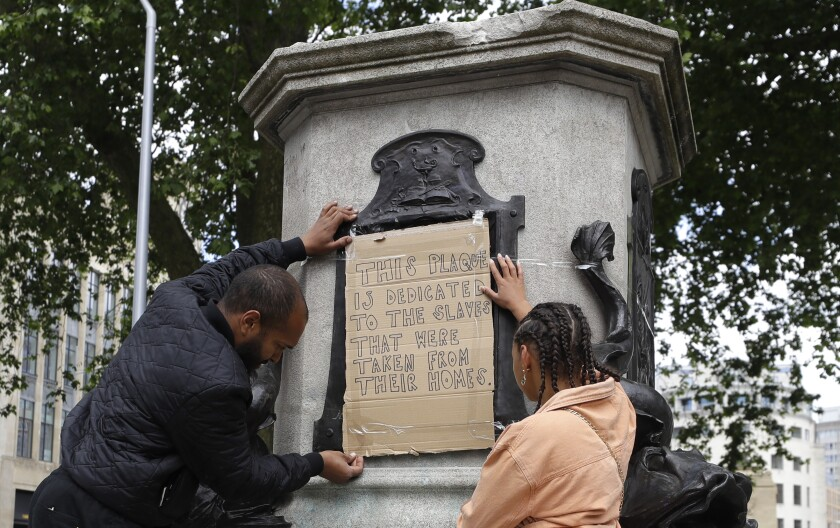 """A A sign taped onto the statue of Edward Colston is dedicated to """"the slaves that were taken from their homes"""""""