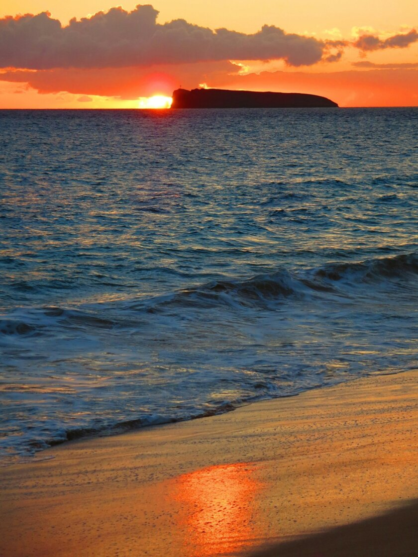 The view of submerged volcano Molokini at sunset is spectacular from the Wailea shore.