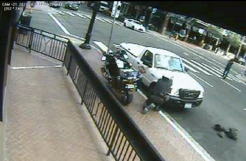 Screen grab from security camera footage of a San Diego police motorcycle officer crouching behind the fender of a pickup truck, foreground, as he fires his weapon at Lamontez Jones, standing at far right, in the Gaslamp nehighborhood, Oct. 20, 2015. The fatal shooting was controversial because some witnesses said officers fired a second volley at him after he was down. Police said Jones raised his pistol - which turned out to be a fake - a second time, and officers feared for their lives. A second motorcycle officer arrived shortly after this frame, and was also involved in the shooting. The two motorcycle officers who fired, Scott Thompson and Gregory Lindstrom, did not turn on their body-worn cameras while they followed him down the street or during the confrontation.