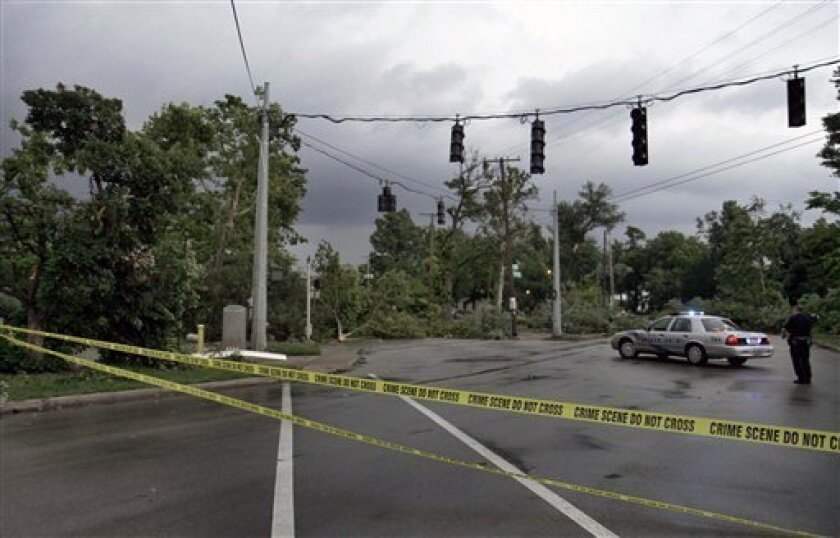 A Louisville police officer stands in the middle of the intersection of Third Street and Southern Parkway just south of Churchill Downs in Louisville, Ky., Wednesday, June 22, 2011 that is blocked in all four directions by downed trees and power lines. An apparent tornado passed through the area knocking out power and damaging barn roofs at the race track. (AP Photo/Garry Jones)