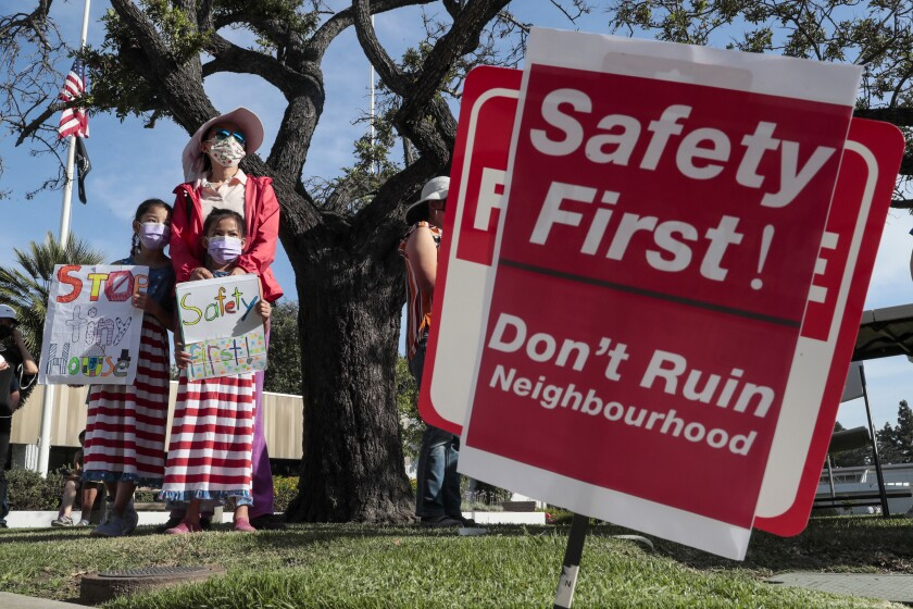 """Behind a sign that says """"Don't ruin neighbourhood,"""" a woman stands with girls holding homemade signs."""