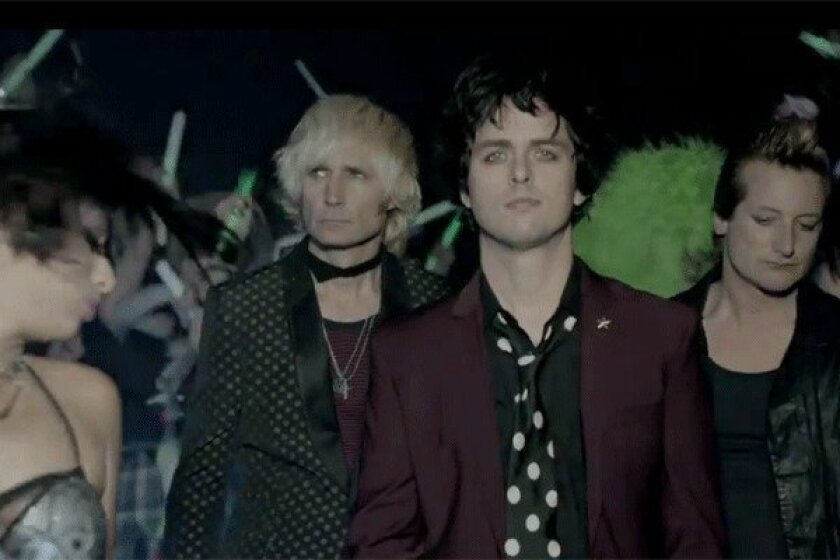 "Green Day's Billie Joe Armstrong, center, with Mike Dirnt, left, and Tre Cool in the video for ""Kill the DJ,"" which is not safe for work."