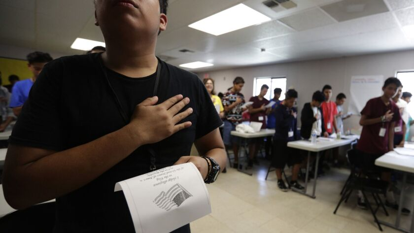 In this Tuesday, July 9, 2019, photo, immigrants say the Pledge of Allegiance in a writing class at