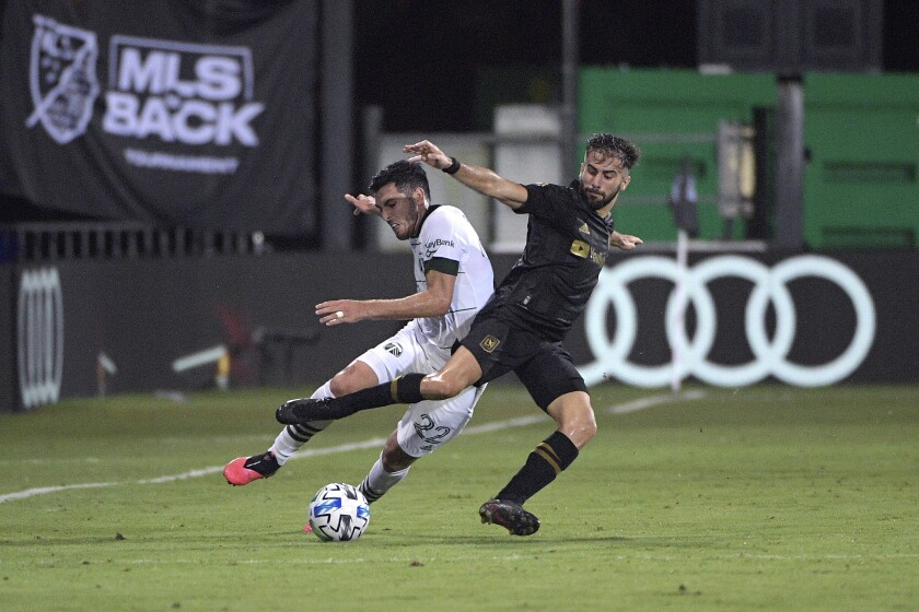 LAFC forward Diego Rossi, right, battles for the ball with Portland Timbers midfielder Cristhian Paredes