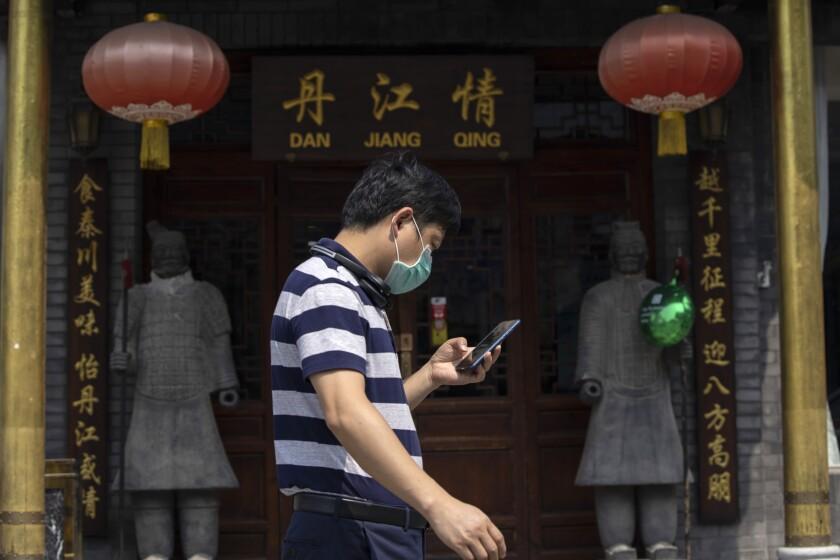 Un hombre con mascarilla pasa frente a un restaurante en Beijing, miércoles 8 de julio de 2020. (AP Foto/Ng Han Guan)