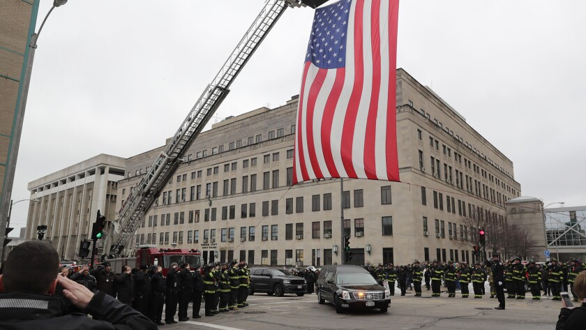 The Milwaukee Fire Department raises a flag at an intersection Feb. 6, 2019, as the hearse containing the casket of a Milwaukee police officer drives past.