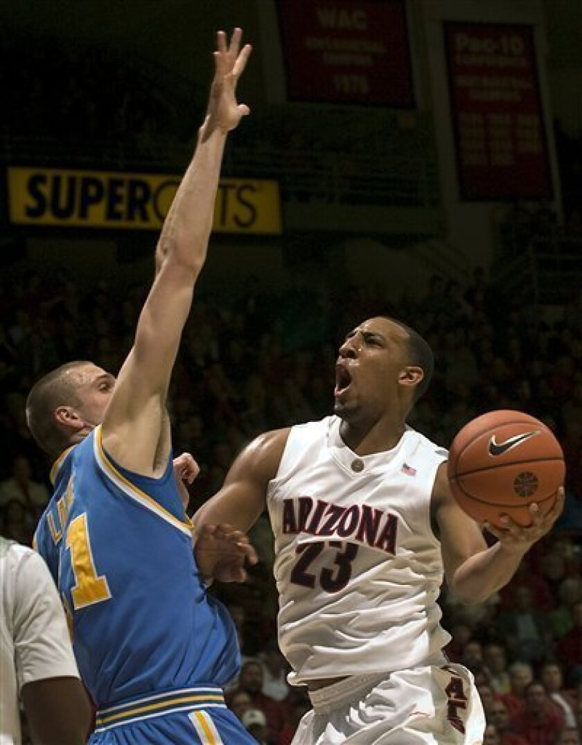 Arizona's Derrick Williams (23) tries to shoot against UCLA's Brendan Lane during the first half of an NCAA college basketball game at McKale Center in Tucson, Ariz., Thursday, March 4, 2010. (AP Photo/John Miller)