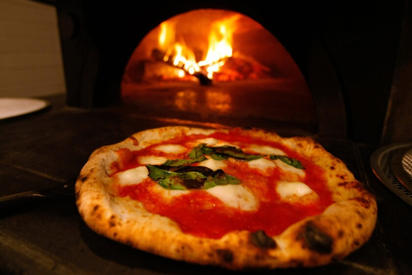 A Margherita pizza with San Marzano tomatoes, buffalo mozzarella and aged Parmigiano-Reggiano comes out of the 850-degree oven at Mother Dough in Los Feliz.