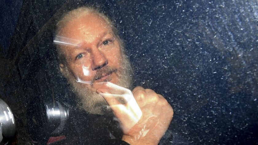 Julian Assange gestures as he arrives at Westminster Magistrates' Court in London, after the WikiLea