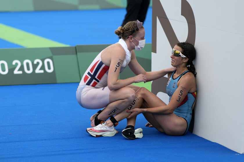 FILE - In this July 27, 2021, file photo, Claire Michel of Belgium is assisted by Lotte Miller of Norway after the finish of the women's individual triathlon competition at the 2020 Summer Olympics, in Tokyo, Japan. In an extraordinary Olympic Games where mental health has been front and center, acts of kindness are everywhere. The world's most competitive athletes have been captured showing gentleness and warmth to one another — celebrating, pep-talking, wiping away each another's tears of disappointment. (AP Photo/David Goldman, File)