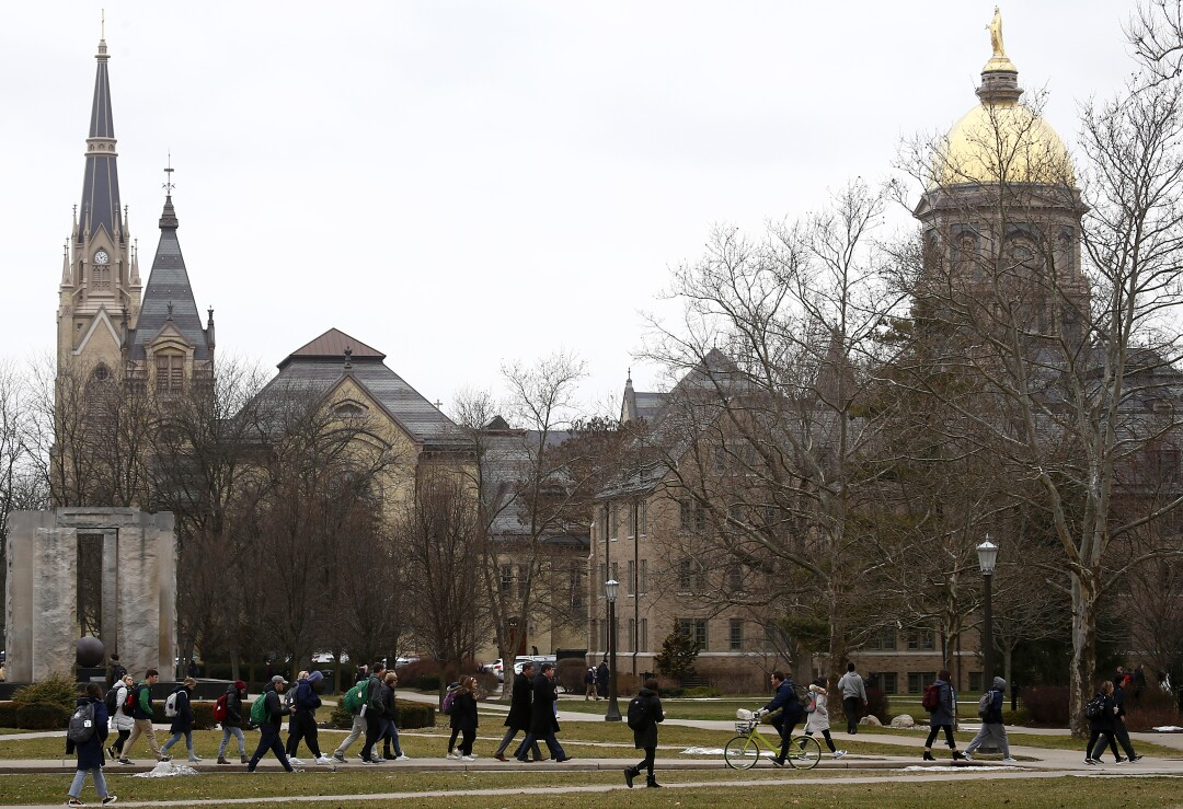 Students walk across the campus of the University of Notre Dame on the outskirts of South Bend, Ind.