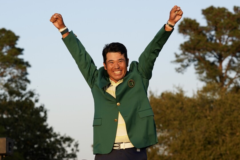 Hideki Matsuyama throws his arms in the air and grins while wearing the winner's green jack at the Masters