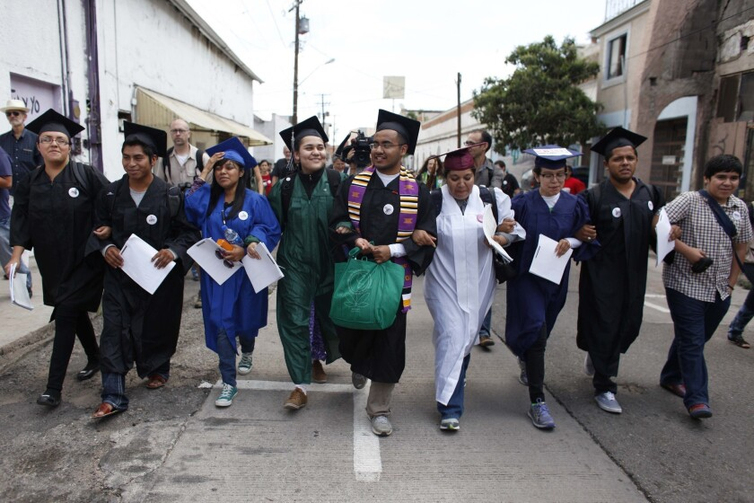 """In July, immigration rights activists, wearing their school graduation caps and gowns to show their desire to finish school in the U.S., marched with linked arms to the U.S. port of entry where they requested humanitarian parole in Nogales, Mexico. The activists, known as the """"Dream 9,"""" were later arrested after attempting to cross the border. They were released from federal custody in August."""