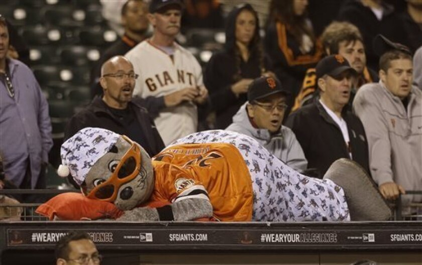 San Francisco Giants mascot Lou Seal wears pajamas and lays on top of the Giants dugout during the fifteenth inning of a baseball game against the New York Mets in San Francisco, Tuesday, July 9, 2013. (AP Photo/Jeff Chiu)