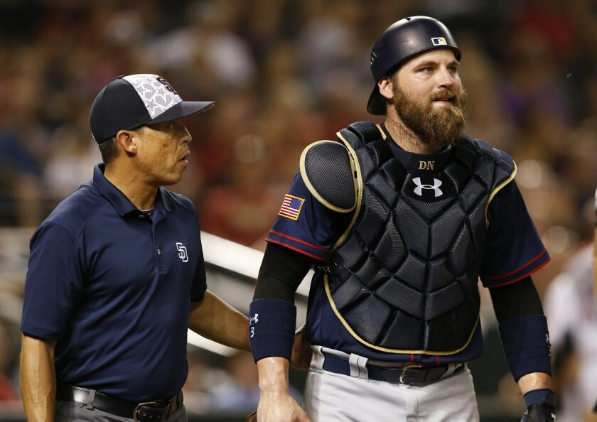 San Diego Padres catcher Derek Norris is helped off the field by team trainer Paul Navarro in the eighth inning after getting hit with a bat on the back swing of Arizona Diamondbacks Brandon Drury during a baseball game, Monday, July 4, 2016, in Phoenix. (AP Photo/Rick Scuteri)