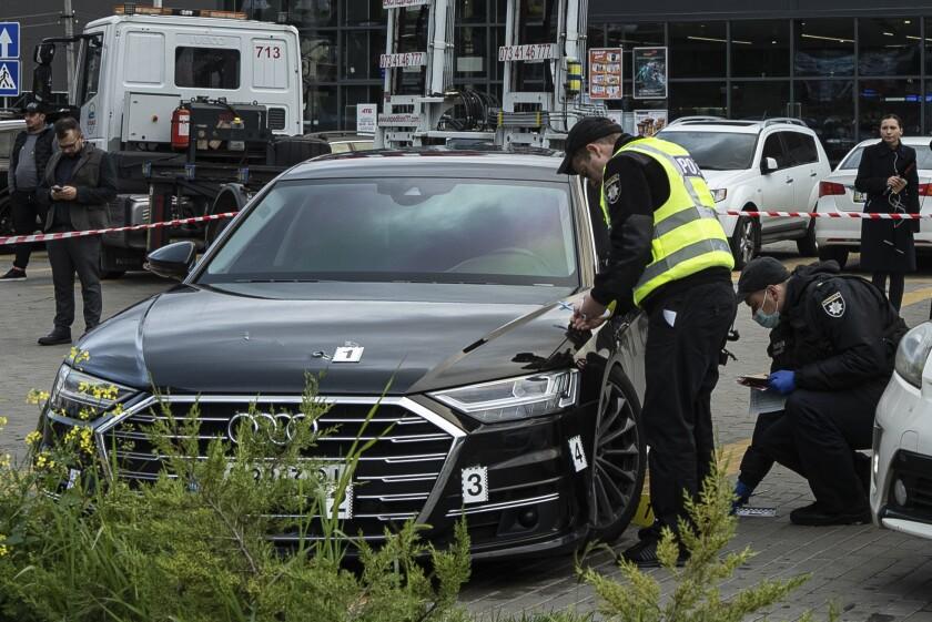 Varios policías recogen pruebas cerca del automóvil de Serhiy Shefir, primer asistente del presidente Volodymyr Zelenskyy, cerca de Kiev, Ucrania, el miércoles 22 de septiembre de 2021. (AP Foto/Evgeniy Maloletka)