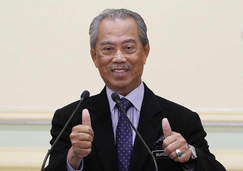 FILE - In this March 9, 2020, file photo, Malaysian Prime Minister Muhyiddin Yassin, thumbs up during a press conference at prime minister's office in Putrajaya, Malaysia. Malaysia's government has issued a directive ordering all civil servants to use the legal spelling of the prime minister's name, Mahiaddin Yasin, after a court earlier squashed a detention order that was signed by the leader using his more widely known unofficial spelling as Muhyiddin Yassin. (AP Photo/Vincent Thian, File)