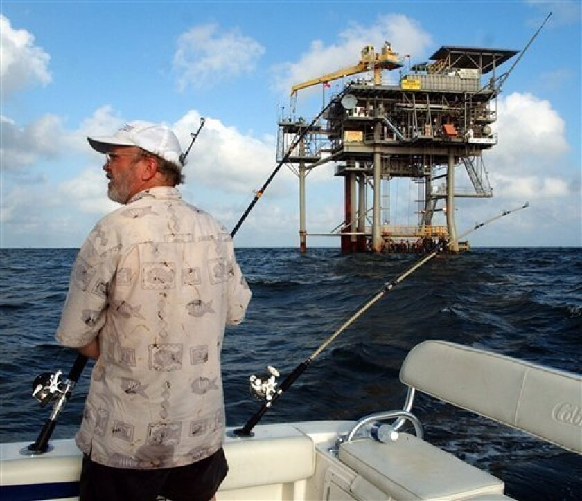 FILE - In a in this Friday, May 9, 2003 file photo, angler Andy Hails, of Montgomery, Ala., checks the fishing lines on his boat as he trolls the Gulf of Mexico near a natural gas well off the Alabama coast near Gulf Shores, Ala. President Obama announced his new offshore drilling policy Wednesday, March 31, 2010. President Obama is allowing oil drilling off Virginia's shorelines and considering it for a large chunk of the Atlantic seaboard. At the same time, he's rejecting some new drilling sites that had been planned in Alaska. (AP Photo/Dave Martin, File)