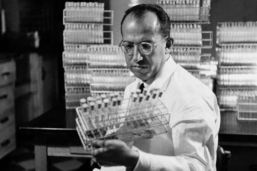 Dr. Jonas Salk, developer of the polio vaccine, holds a rack of test tubes in his lab in Pittsburgh in October 1954.