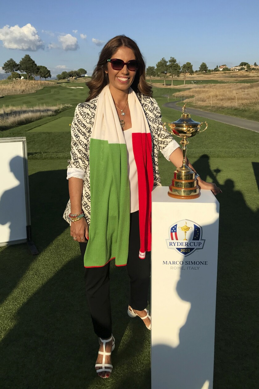 Lavinia Biagiotti Cigna poses by the Ryder Cup trophy at the Marco Simone Golf and Country Club, in Guidonia, on the outskirts of Rome, Wednesday, Sept. 1, 2021. An 11th-century castle. A grove of olive trees. The remains of an ancient Roman villa. Views of St. Peter's Basilica on the horizon. The terrain surrounding and comprising the Marco Simone Golf and Country Club on Rome's outskirts that will host the 2023 Ryder Cup is quintessential Italy. And no one knows that better than fashion designer Lavinia Biagiotti Cigna, who owns and runs the club. Biagiotti Cigna also lives on the club grounds with her three dogs — in the castle, of course, which is situated between a bend in the course wedged between the sixth and eighth holes. Astronomer Galileo Galilei once lived in the castle, too. (AP Photo/Andrew Dampf)