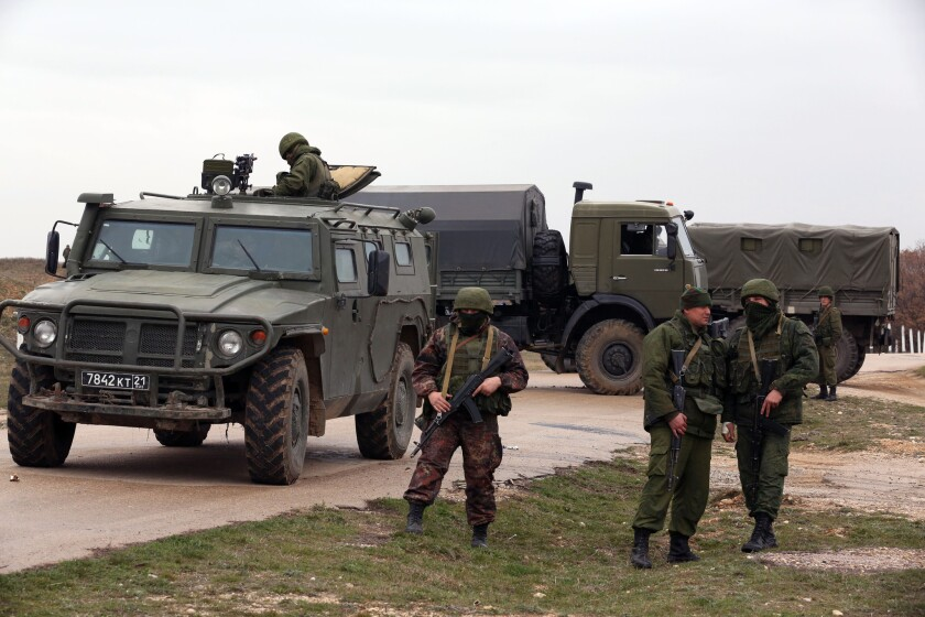 Russian-speaking troops in unmarked uniforms stand guard at the airport of Belbek, which they captured from the Ukrainian army. The Tigr combat vehicle in the photo has Russian army license plates.