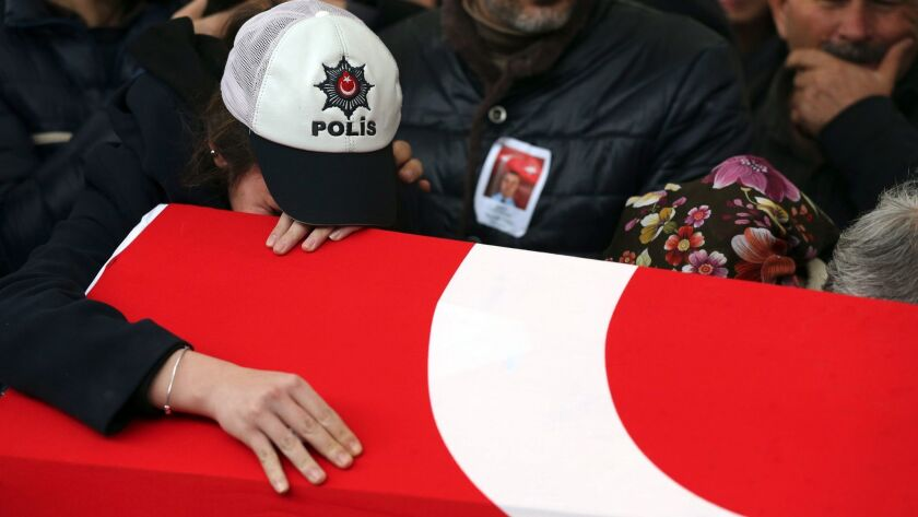 Relatives of police officer Hasim Usta, who was killed in bomb attacks Saturday, mourn over his coffin during the funeral Monday in Istanbul, Turkey.