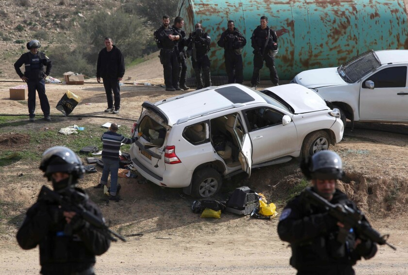 Israeli policemen stand guard next to a car, reportedly used in a ramming attack that left one police officer dead. Police shot and killed the driver.