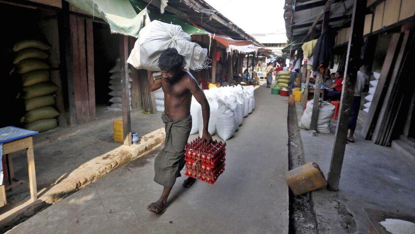 A Muslim man carries goods inside the market in ButheeTaung town, Rakhine State, western Myanmar.