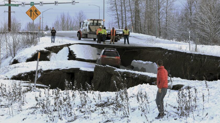 Highway workers and spectators look at a car stuck on a section of an off-ramp that collapsed during