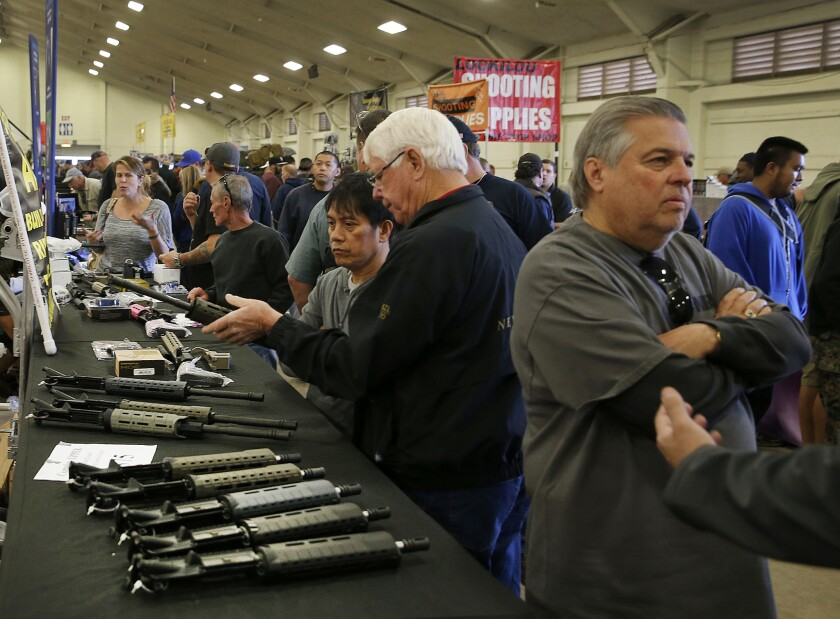 Gun enthusiasts view AR-15 semi-automatic assault rifle upper receiver parts and kits, which are legal in California, at the Crossroads of The West Gun Show in Del Mar, Calif. last year