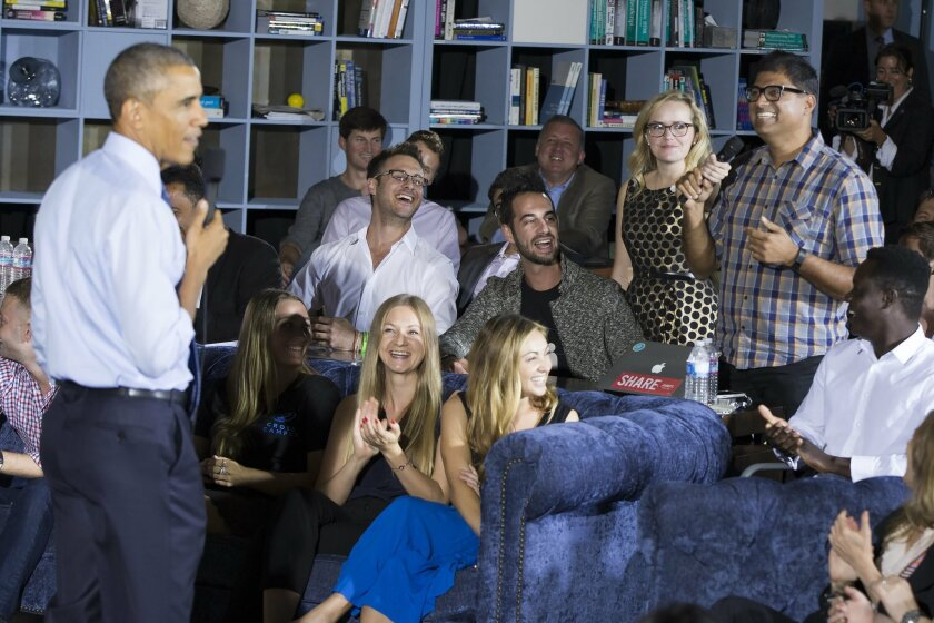 Co-founder of Sensay Ariel Jalali, right, offers a job to President Barack Obama when his presidential term is over, during an event at Cross Campus, a collaborative space that brings together freelancers, creative professionals, entrepreneurs and startup teams, on Thursday, Oct. 9, 2014, in Santa Monica. Obama is traveling in Los Angeles for an overnight trip during which he will discuss the nation's economy and designate a swath of Southern California mountains as a national monument. (AP Photo/Evan Vucci)