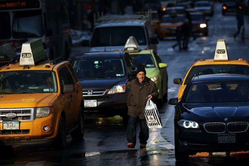 A pedestrian walks in traffic in New York