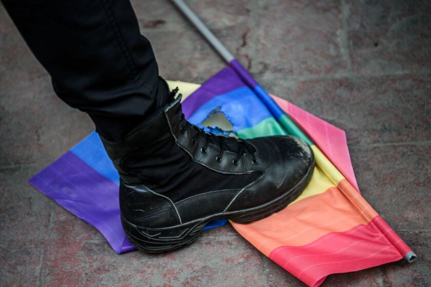 A Turkish anti-riot police officer steps on a rainbow flag during a rally staged by the LGBT community in Istanbul on June 19, 2016.