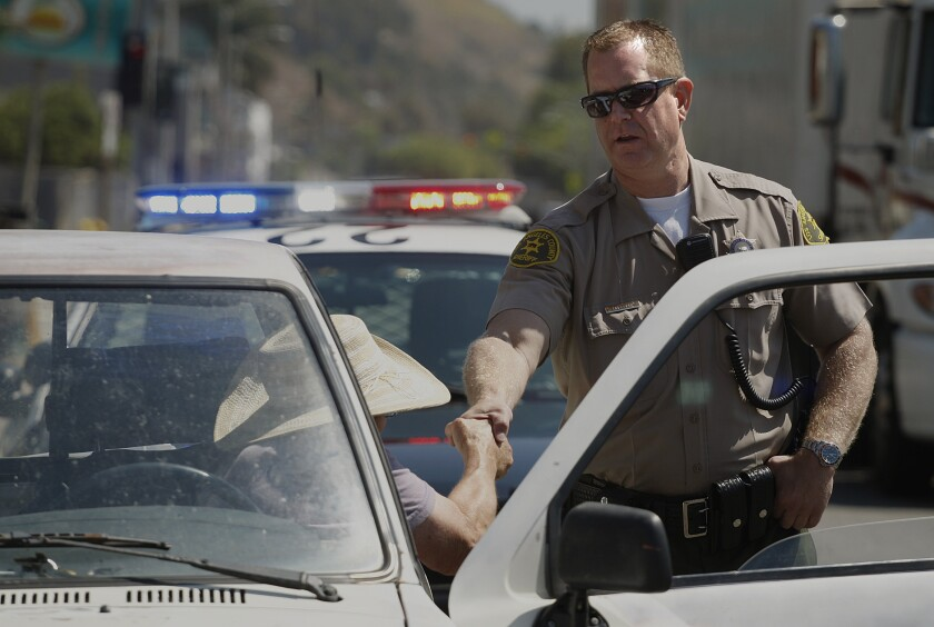 David Huelsen, a traffic detective with the L.A. County Sheriff's Department, shakes a motorist's hand in Malibu. Huelsen is participating in the department's program to photograph detainees who don't have IDs.