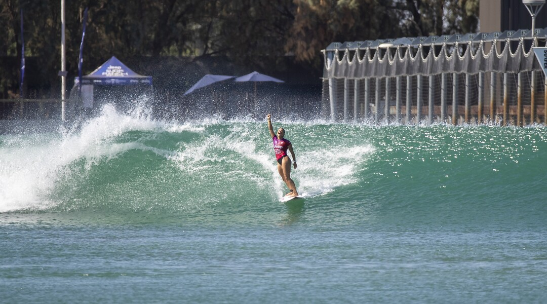 Johanne Defay raises her arm in victory while riding a wave