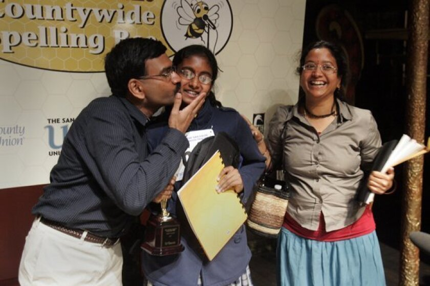 The 42nd annual San Diego Union-Tribune Countywide Spelling Bee was held Tuesday at the Old Town Theater. The eventual winner, Snigdha Nandipati, center, got a kiss from her father Krishnarao Nandipati, left, while her mother Madhavi Nandipati smiles beside her..