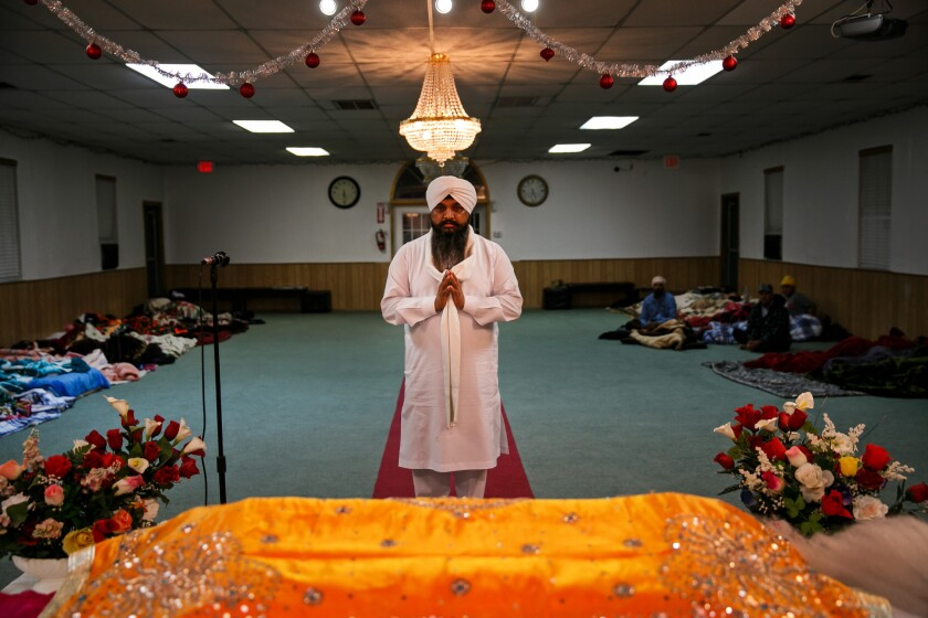 Nirmal Singh, a Sikh priest, conducts a morning prayer ritual as evacuees sleep in the background at Shri Guru Ravidass, a Sikh temple in Rio Linda, Calif., that opened its doors amid the Oroville Dam crisis.