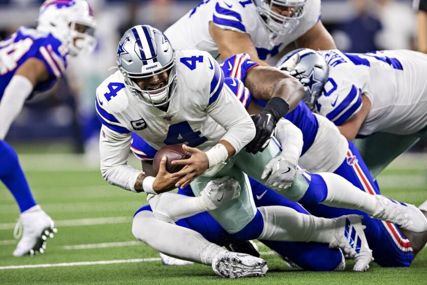 Dallas Cowboys quarterback Dak Prescott runs with the ball.