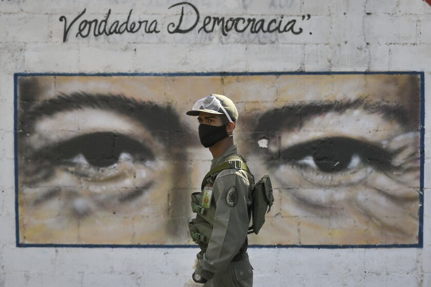 A soldier guards a voting poll at a school that has the eyes of the late President Hugo Chavez painted on a wall during elections to choose members of the National Assembly in Caracas, Venezuela, Sunday, Dec. 6, 2020. The vote, championed by President Nicolas Maduro, is rejected as fraud by the nation's most influential opposition politicians. (AP Photo/Matias Delacroix)