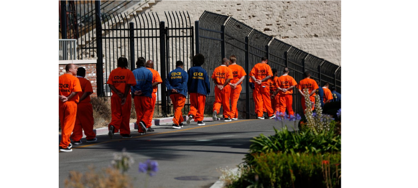 Inmates walk in file in front at San Quentin State Prison