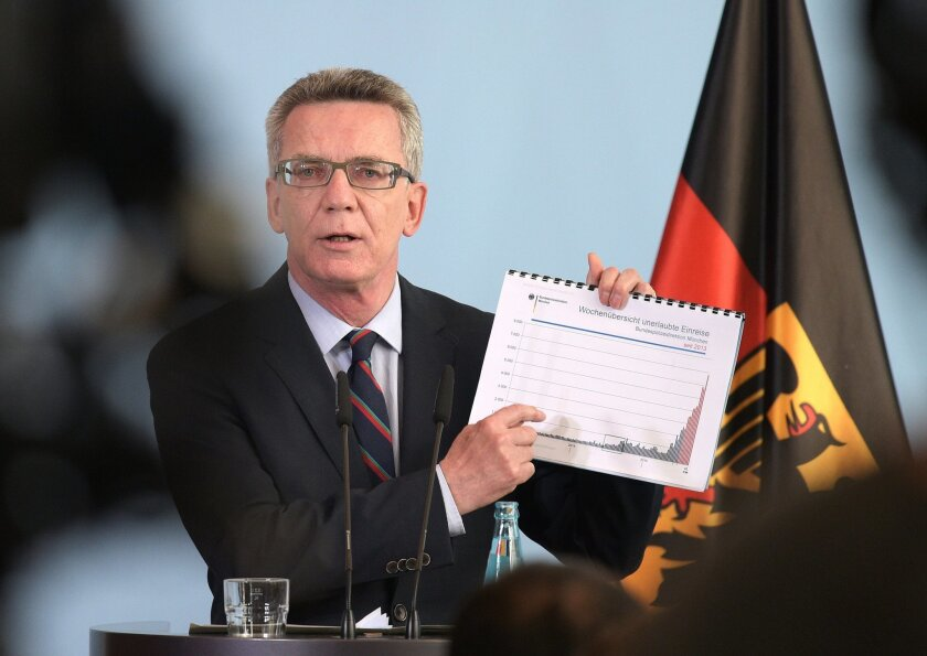 German interior minister Thomas de Maiziere attends a news conference in Berlin, Germany, Wednesday Aug. 19, 2015. Germany could see as many as 800,000 migrants in 2015, the country's interior minister said Wednesday, four times the number last year and 300,000 more than previously estimated. (Rainer Jensen/dpa via AP)