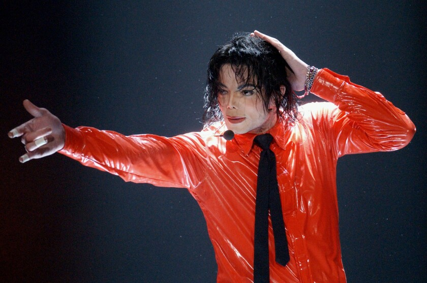 """FILE - Michael Jackson performs """"Dangerous"""" during the taping of the American Bandstand's 50th anniversary show on April 20, 2002, in Pasadena, Calif. With a series of court victories and shows beginning or returning after a long pandemic pause, Jackson's estate, and his legacy are on the upswing again. Estate co-executor John Branca said in an interview with The Associated Press that his optimism never flagged as crises hit. (AP Photo/Kevork Djansezian, File)"""