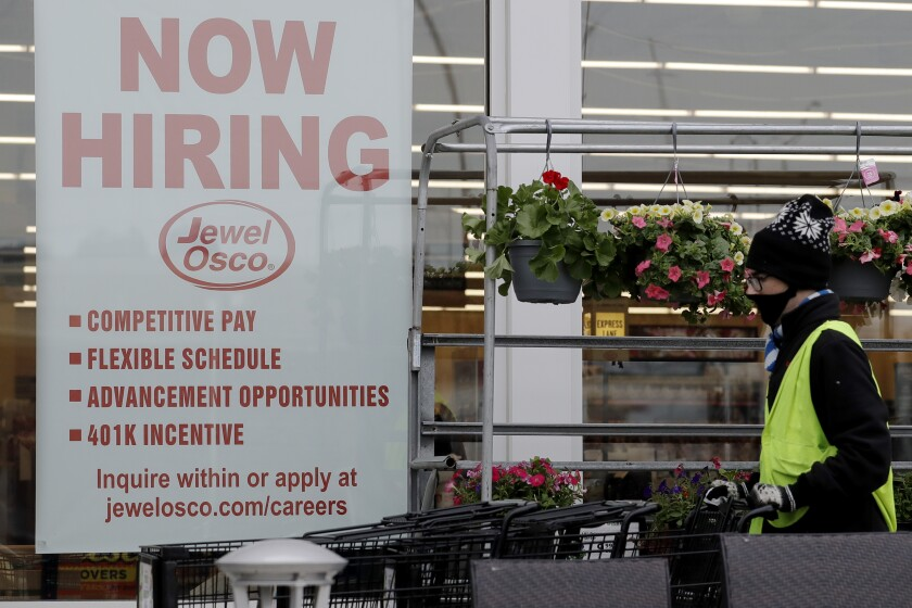 "A man pushes carts next to a ""now hiring"" sign at a grocery store in Deerfield, Ill."