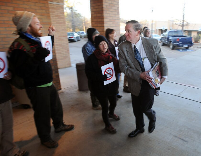 Michael Bishop, right, is cheered by supporters as he heads into the Nacogdoches County Courthouse on Thursday. Bishop is battling TransCanada, which wants to build the Keystone XL oil pipeline across his land in East Texas.