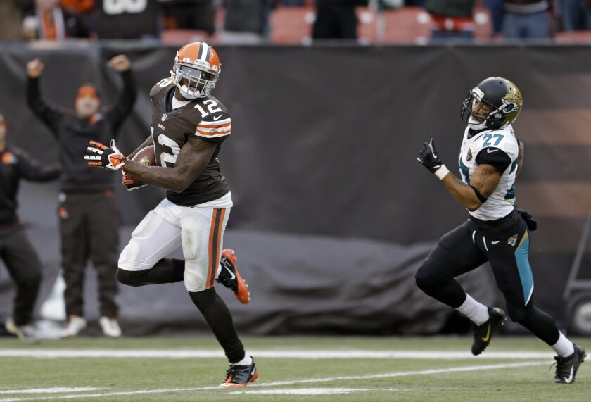 Cleveland Browns wide receiver Josh Gordon (12) outruns Jacksonville Jaguars cornerback Dwayne Gratz (27) on a 95-yard touchdown reception in the fourth quarter of an NFL football game on Sunday, Dec. 1, 2013, in Cleveland. (AP Photo/Tony Dejak)