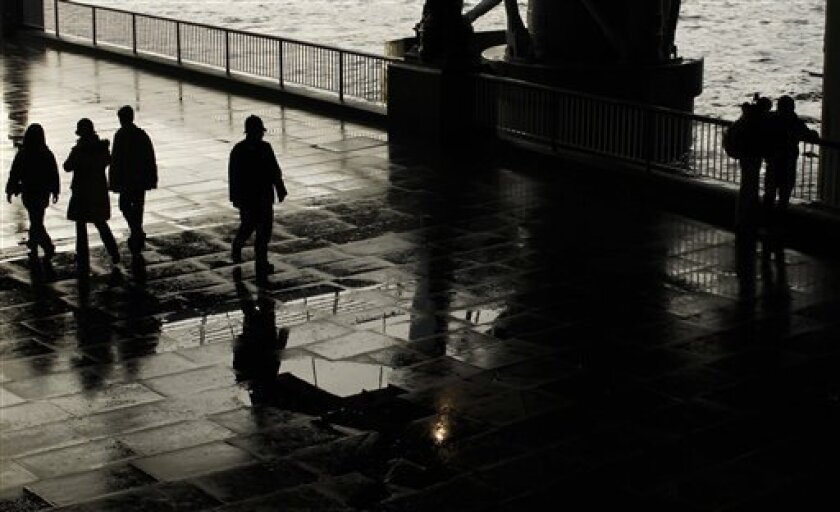 A patrolling police officer, center, is silhouetted by the darker light under a bridge on the South Bank by the River Thames as he looks over at an embracing couple, at right, after a rain shower in London, Friday, Jan. 7, 2011. Police patrolled transport hubs across London on Friday amid continuing fears of a terrorist attack. Britain's media said the security threat level for airports and railway stations has been raised, as governments in several European countries warn of a heightened risk of terrorism. (AP Photo/Matt Dunham)
